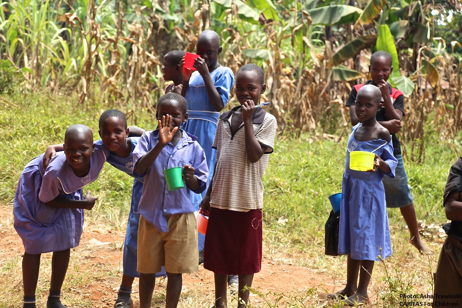 an image of Ugandan children waving with cups