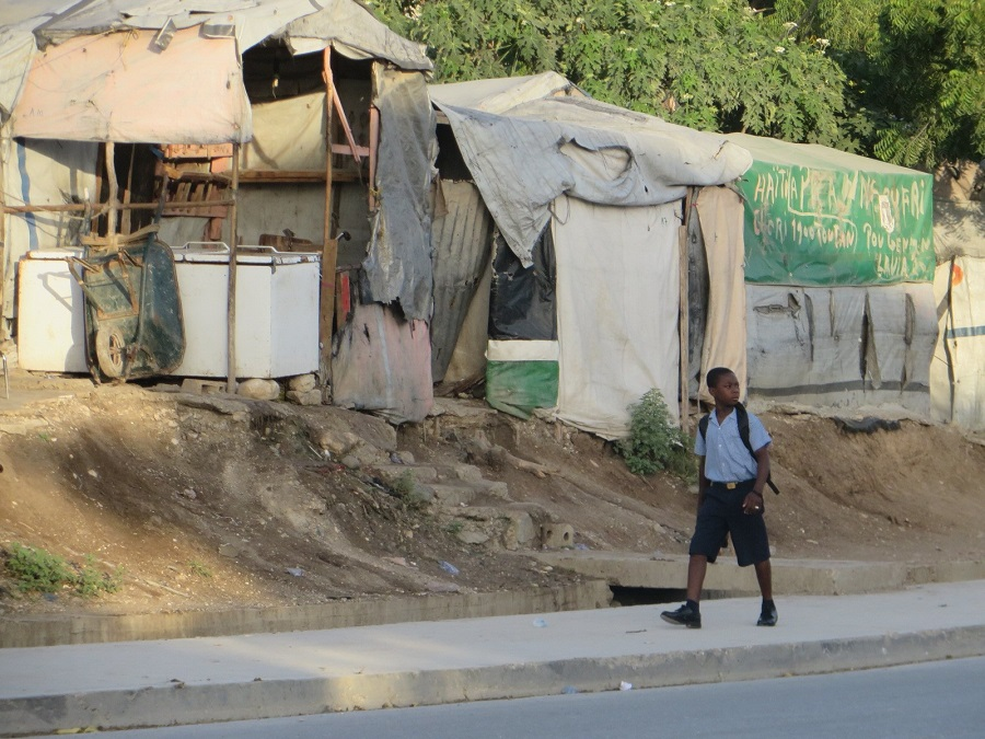 boy walking past dilapidated shelters in Haiti