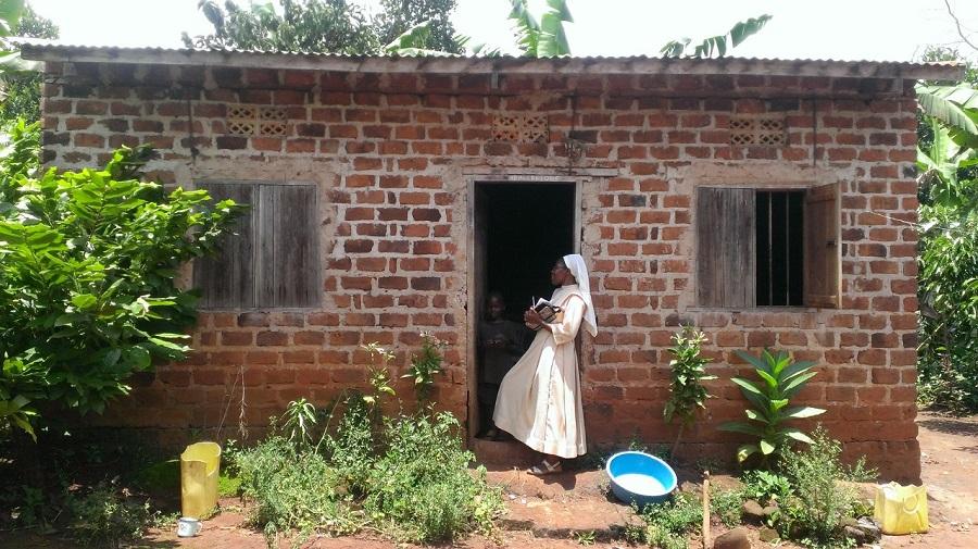 Sr. Carolyne, CARITAS For Children Program Coordinator in Uganda, approaches the family home of hand-made, red bricks in Maseke