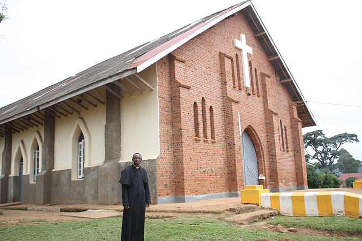 Fr. John Bosco in front of his local church, Our Lady Queen of Apostles in Nkokonjeru