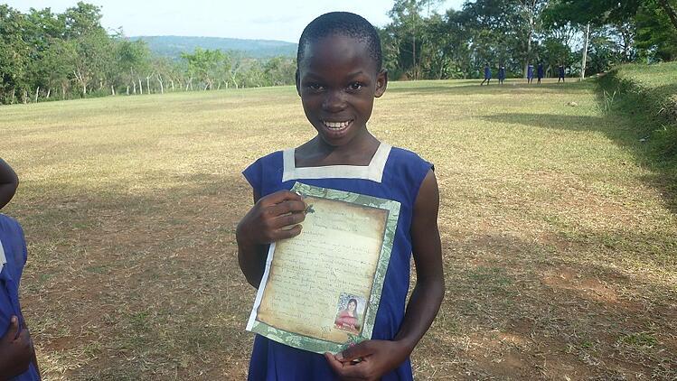 Ugandan girl from Catholic child sponsorship program holding letter