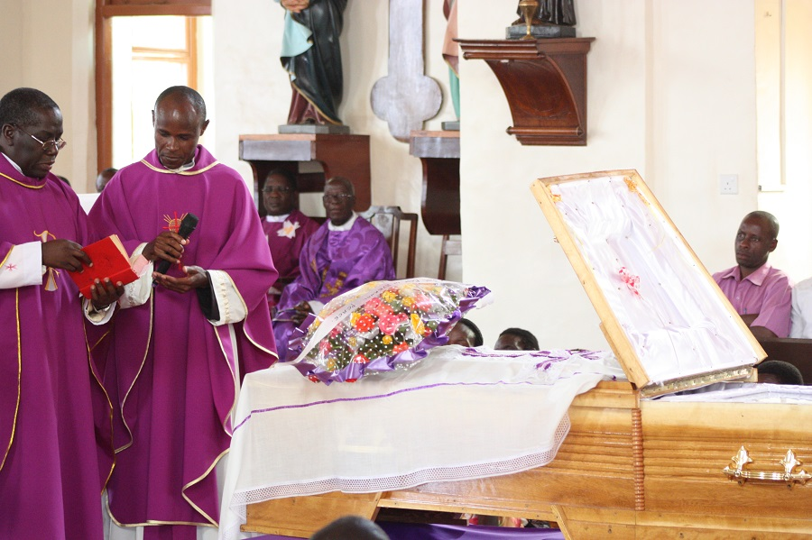 The priests give the final blessing over the late sister's grave