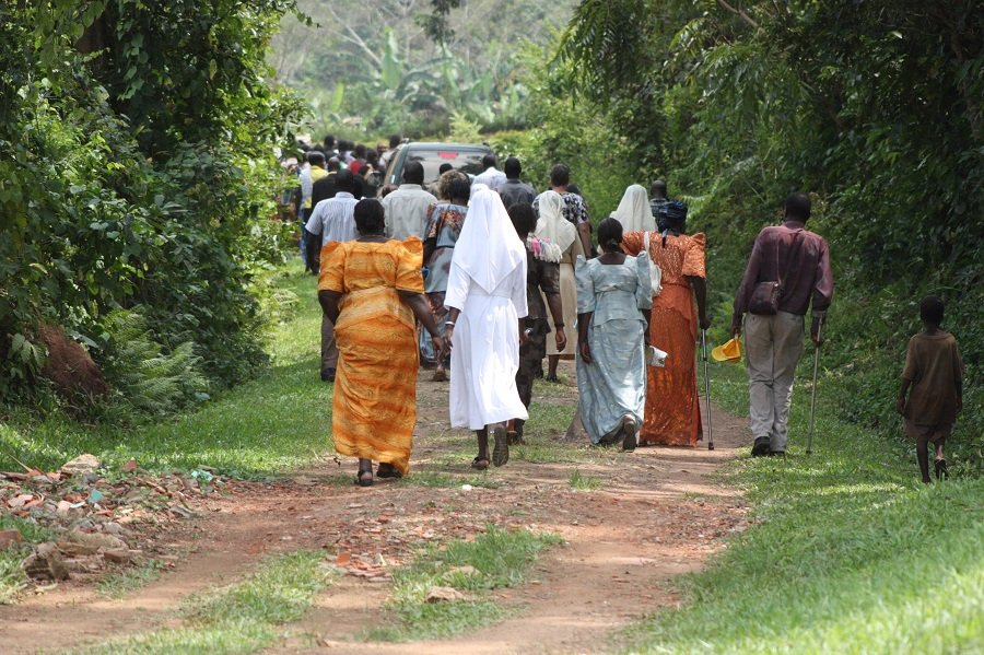 The mourners walk to the graveyard to witness the burial the late sister.