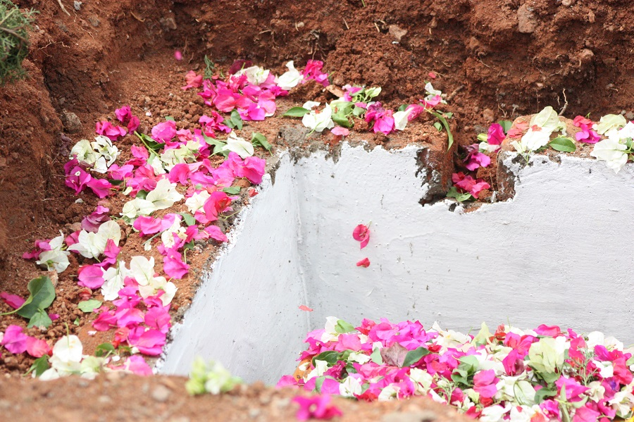 Flowers are dropped into sister's grave by every burial attendee