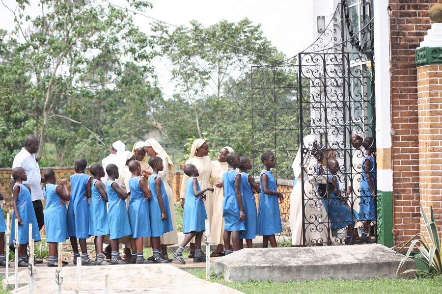 Children from Stella Maris Primary Boarding School, including CARITAS' own Martha Mbejjo, go to Mother Kevin to leave their prayer intentions