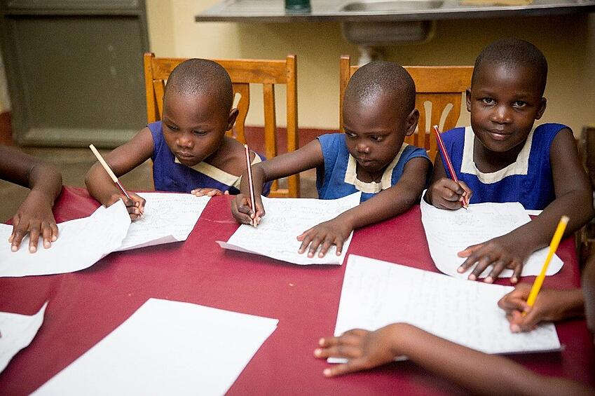 CARITAS Children Butono Veronica, Daphine Nakayiza, and Mirembe Grace writing letters to their sponsors (Photo Credit: Tina LeAnn Photography)