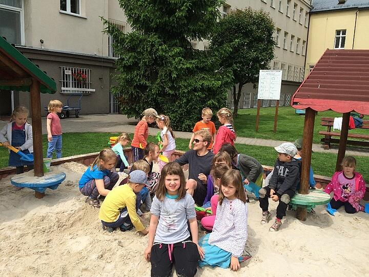 image of young man surrounded by children in sandbox
