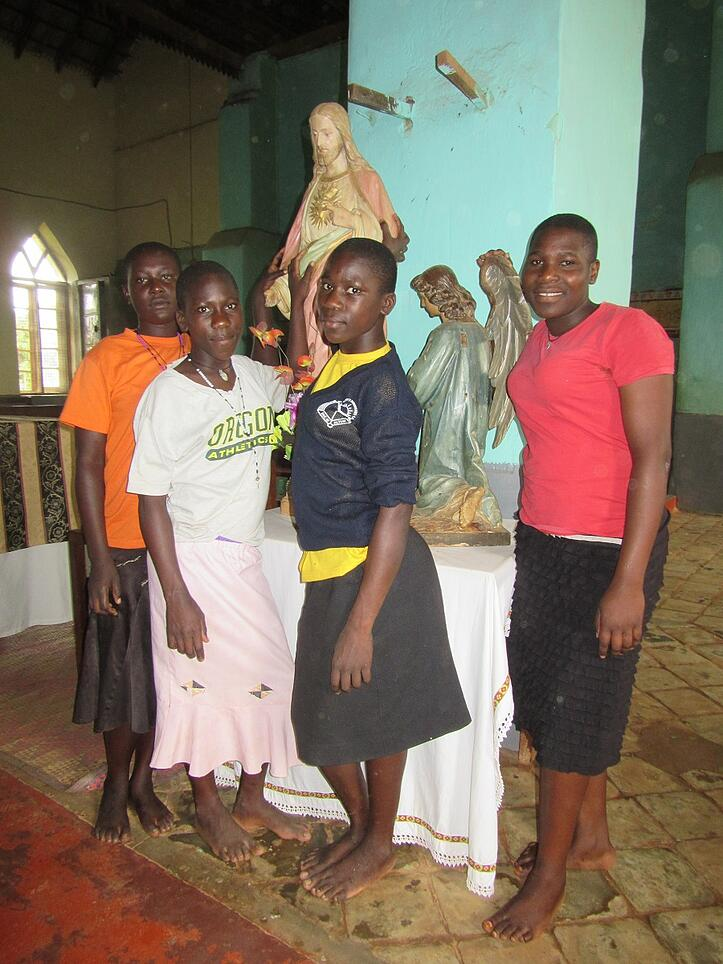Four teen girls posing by statue of Jesus.