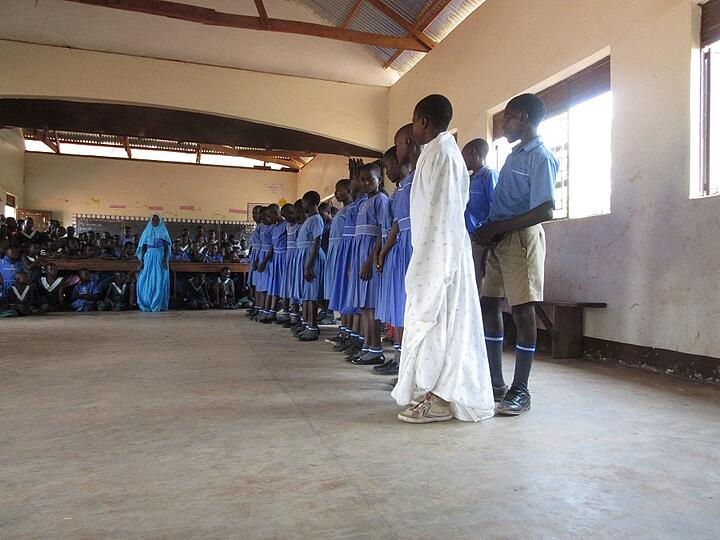 Students from St. Paul Boys School present a song about Mother Mary. Despite the name of the school, the student population is co-ed.