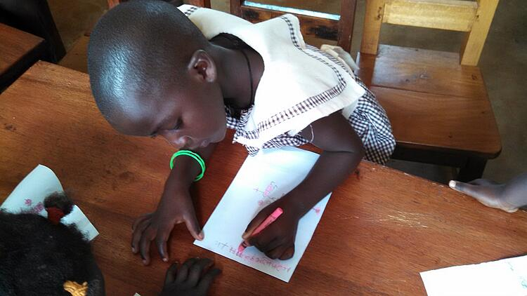 A student from baby class, three to four-year-olds, enjoy coloring with a gift of new crayons.