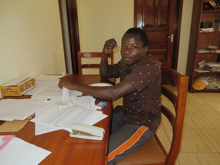 James writing at the desk of the CARITAS Residential Learning Center